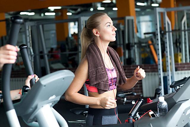 スポーツジムでイヤホンをしながら走っている女性の写真