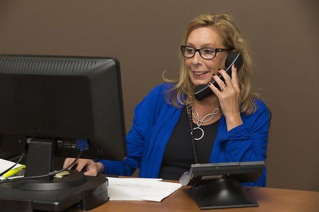 パソコンを見ながら電話で注文をする女性