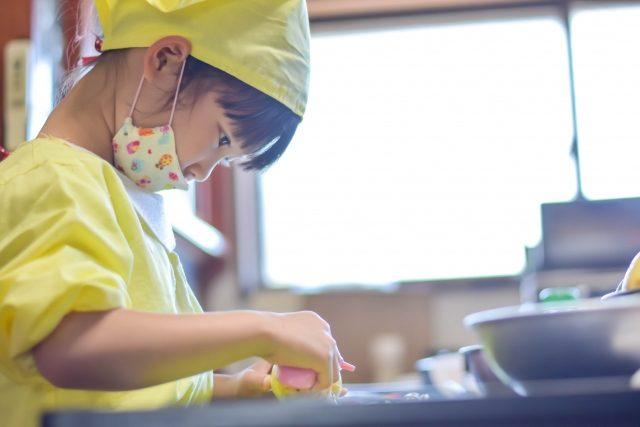 子どもがマスクをして料理をしている写真
