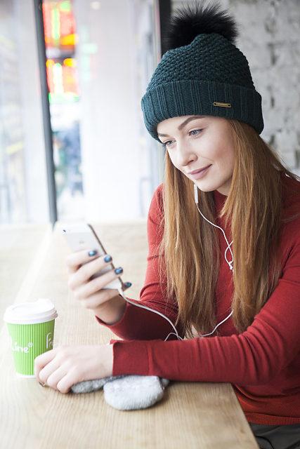 カフェでイヤホンをしながらくつろいでいる女性の写真