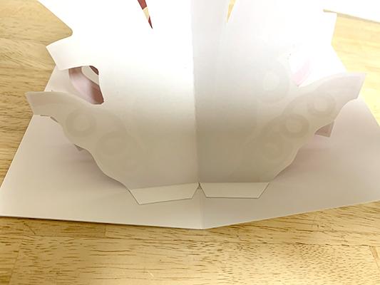 1枚の紙にプリントして各パーツを抜き型で抜いているかと思いきや、細かいカーブの切り口を拡大して見ると、どうやら1つずつ手作業でカットしているみたい。それを山折りして中央に両面テープで切り貼りして立ち上がるように作っているようです。派手な色使いやデザインは悪くはないけど、土台のカードが白いままというのが少し寂しい気もするなぁ。ここに手書きでメッセージを書けってことかな。
