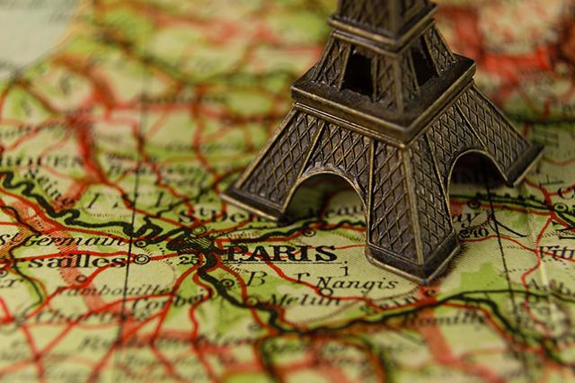 フランス・パリの地図の上にエッフェル塔の模型が置いてある様子