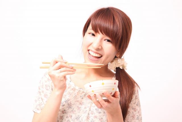 お茶碗と箸を持つ女性のイメージ写真