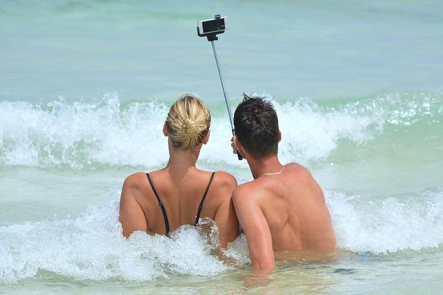 砂浜で波を受けながら自撮りをするカップル