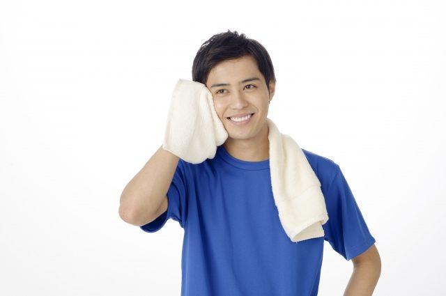 タオルで汗を拭く男性
